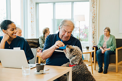 Smiling female nurse looking at senior man feeding dog in retirement home - p426m2149341 by Maskot