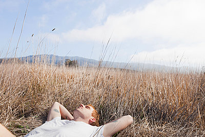 Man resting in field - p956m1044283 by Anna Quinn
