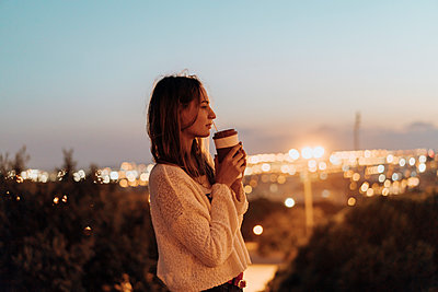Spain, Barcelona, Montjuic, young woman holding takeaway drink at dusk with city lights in background - p300m2058594 by VITTA GALLERY