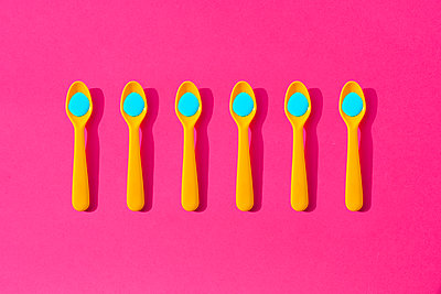 Studio shot of row of yellow plastic teaspoons with blue liquid - p300m2198267 by Gemma Ferrando