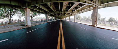 Empty highway next to cemetery, New York City, USA - p3012188f by fStop