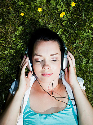 Girl with headphones in the grass - p4265619f by Tuomas Marttila