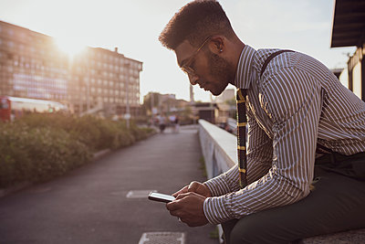 Businessman using smartphone by pavement, Milano, Lombardia, Italy - p429m2097680 by Eugenio Marongiu
