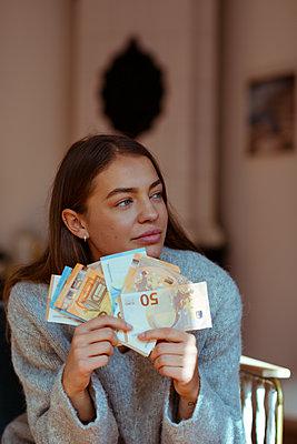 Junge Frau hält Euro-Geldscheine in der Hand - p432m2028632 von mia takahara