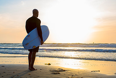 Mixed race man holding surfboard on beach - p555m1418750 by Inti St Clair