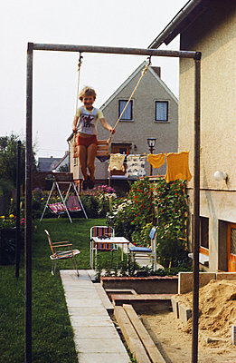 Boy on a swing in the garden, GDR, 1983 - p986m2177968 by Friedrich Kayser