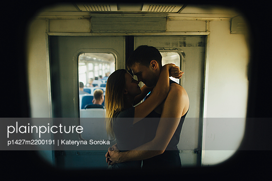 Young couple kissing in train - p1427m2200191 by Kateryna Soroka