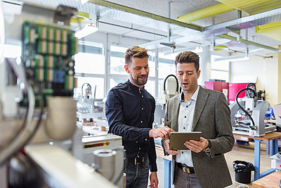 Two businessmen with tablet talking in factory - p300m1587645 by Daniel Ingold