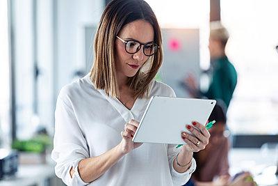 Female entrepreneur using digital tablet in office - p300m2167181 by Josep Suria