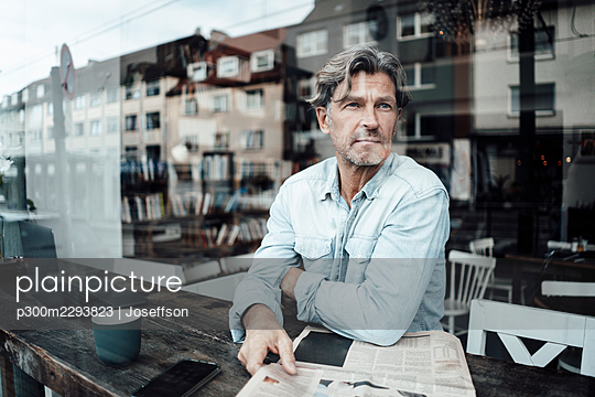 Mature man sitting with newspaper in cafe seen through glass window - p300m2293823 by Joseffson
