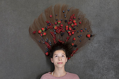 Portrait of girl lying on floor and fruits on hair - p300m2062273 by Petra Stockhausen