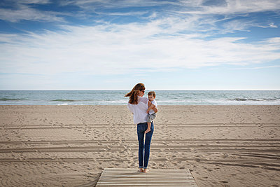 Rear view of mid adult woman carrying toddler daughter on beach, Castelldefels, Catalonia, Spain - p429m1013820f by Quim Roser