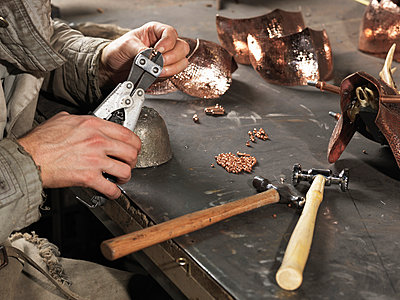 Cropped image of blacksmiths hands working with copper rivets - p429m935443 by Elke Meitzel