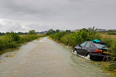 Car forced off the road by flood water sweeping from field to field in Lyneham - p871m884421 by Tim Graham