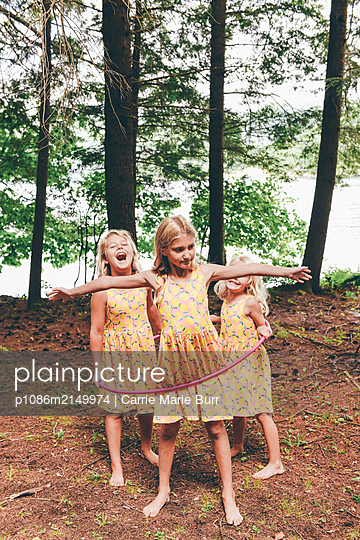 Siblings playing with the Hula-Hoop - p1086m2149974 by Carrie Marie Burr