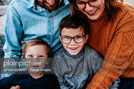 Close up of two happy boys sitting on parents lap - p1166m2208507 by Cavan Images