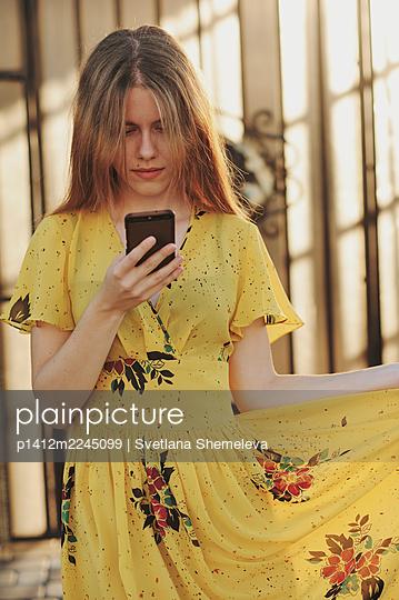 Porträt einer jungen Frau in gelbem Kleid - p1412m2245099 von Svetlana Shemeleva