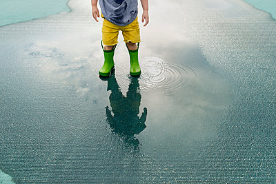 Low section of boy in rubber boots standing in puddle - p1166m1186131 by Cavan Images