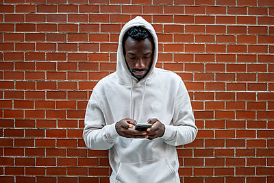Front shot of African man with serious gesture and hood using smartphone in city - p1166m2235375 by Cavan Images
