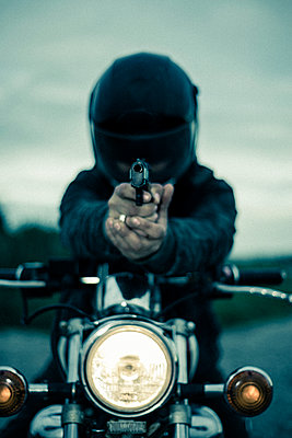 Man wearing crash helmet on a vintage 1980s motorbike,  pointing a handgun - p1433m1582877 by Wolf Kettler