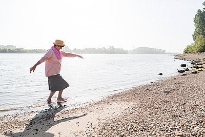 Germany, Ludwigshafen, senior woman walking out of Rhine River - p300m1069034f by Uwe Umstätter