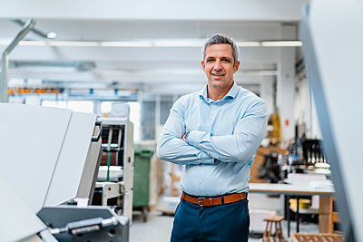 Portrait of a confident businessman in a factory - p300m2159991 by Daniel Ingold