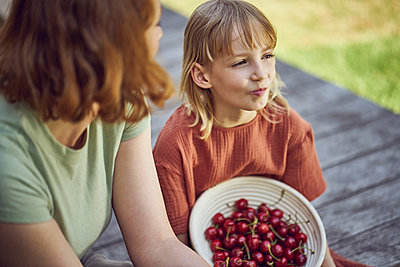 Close-up of mother and daughter eating cherries while sitting in yard - p300m2214216 by Maya Claussen
