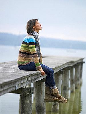 Frau sitzt auf einem Steg am See  - p6430098 von senior images