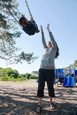 Smiling Mid-Adult Woman Pushing Child in Playground Chair Swing  - p694m2065378 by Novo Images