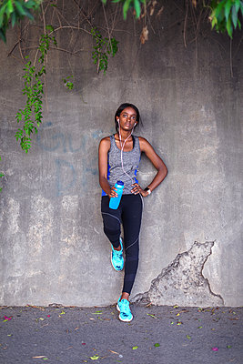 Young female runner listening to earphones leaning against city sidewalk wall, portrait - p924m2090585 by Bean Creative