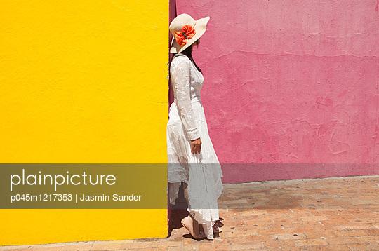 Frau steht an Wand - p045m1217353 von Jasmin Sander