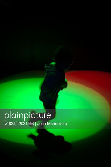 Young boy playing under spotlights - p1028m2021554 von Jean Marmeisse