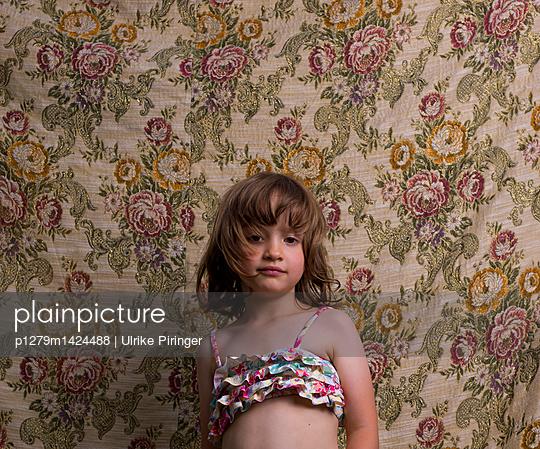 Girl wearing bikini top against floral wallpaper - p1279m1424488 by Ulrike Piringer