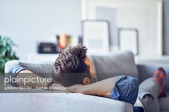 plainpicture - plainpicture p300m1567761 - Relaxed man lying on sofa - plainpicture/Westend61/Bartek Szewczyk