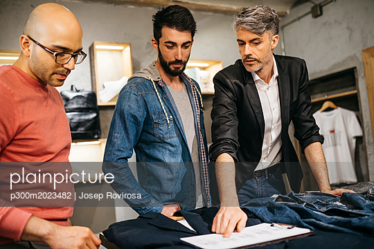 Casual man standing in boutique with stylists and discussing new modern outfit in team - p300m2023482 von Josep Rovirosa