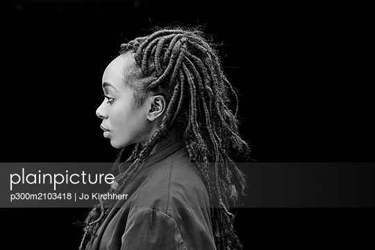 Profile of woman with dreadlocks in front of black background - p300m2103418 by Jo Kirchherr