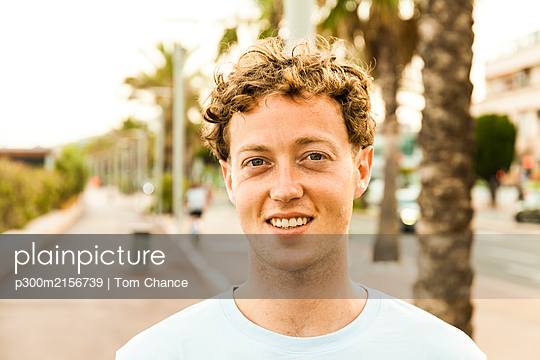 Portrait of smiling young strawberry blonde man - p300m2156739 by Tom Chance