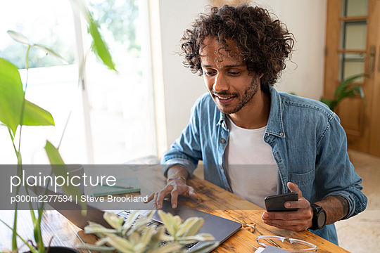 Young businessman holding smart phone while using laptop at home - p300m2277594 by Steve Brookland