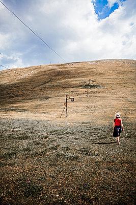 Woman hiking across fields - p075m1474727 by Lukasz Chrobok