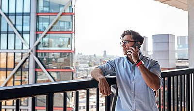 UK, London, man on the phone on a roof terrace - p300m2062098 by Marco Govel