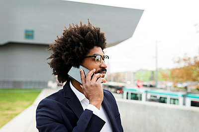 Spain, Barcelona, portrait of businessman on cell phone in the city - p300m2104415 by Valentina Barreto