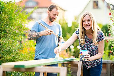 Blond woman painting wooden plank with boyfriend standing in garden - p300m2264558 by Annika List
