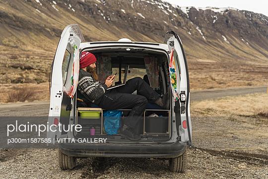 Iceland, man sitting in van using smartphone and laptop - p300m1587585 von VITTA GALLERY