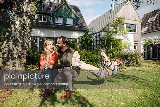 Son swinging in garden with parents next to him - p300m2167301 by Kniel Synnatzschke