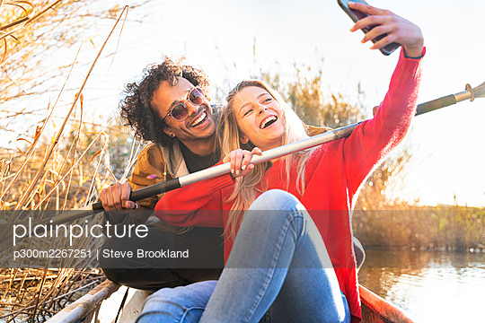Happy couple taking selfie with oar through mobile phone while sitting in canoe on river - p300m2267251 by Steve Brookland