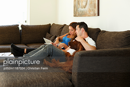 Sweden, Couple with dog sitting on sofa