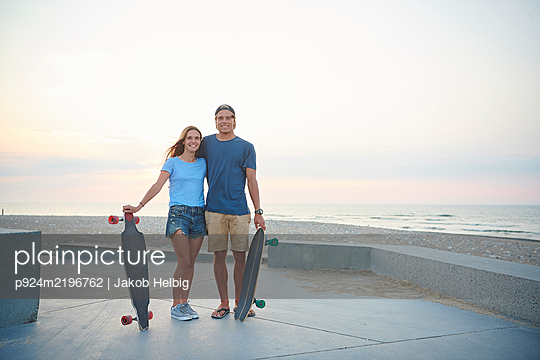A young couple, man and woman skateboarding by the beach at sunset. - p924m2196762 by Jakob Helbig