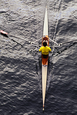 A man sculling in a single scull rowing boat, on the water.  Overhead view.  - p1100m1220573 by Mint Images