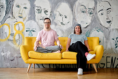 Man with Down's syndrome on a sofa alongside girlfriend - p1164m2175916 by Uwe Schinkel