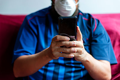 Close-up of a person using his smartphone in quarantine - p1166m2179531 by Cavan Images